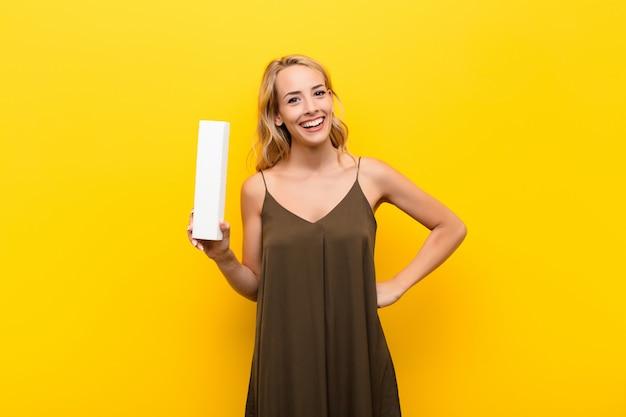 Jonge blonde vrouw opgewonden, blij, vrolijk, met de letter i van het alfabet om een woord of een zin te vormen.