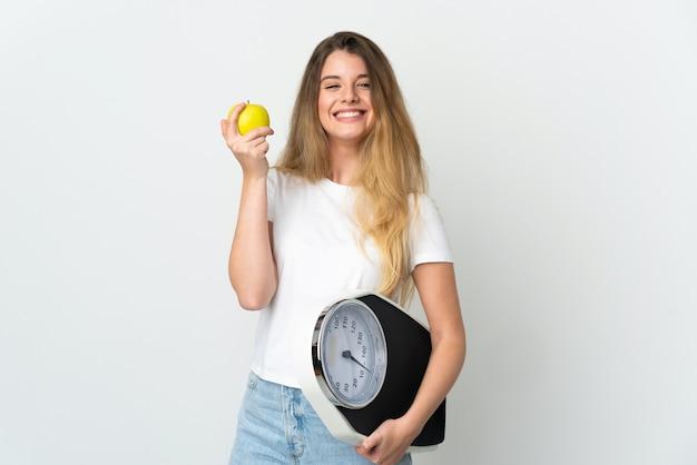 Jonge blonde vrouw over geïsoleerd met weegmachine en met een appel