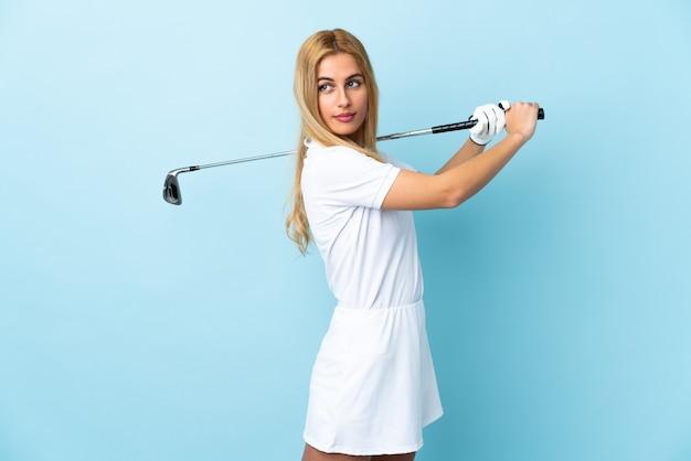 Jonge blonde vrouw over geïsoleerde blauwe golf