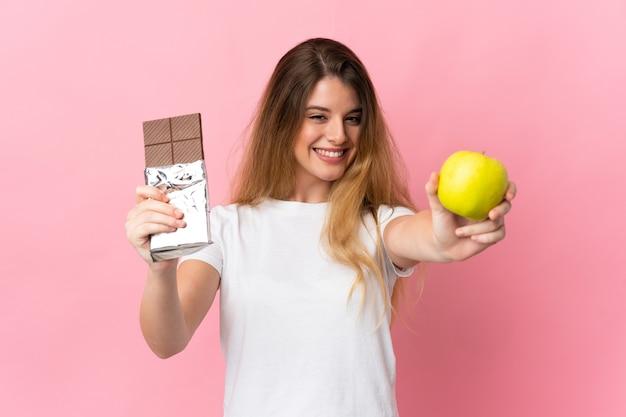 Jonge blonde vrouw over geïsoleerde muur die een chocoladetablet in één hand en een appel in andere hand neemt