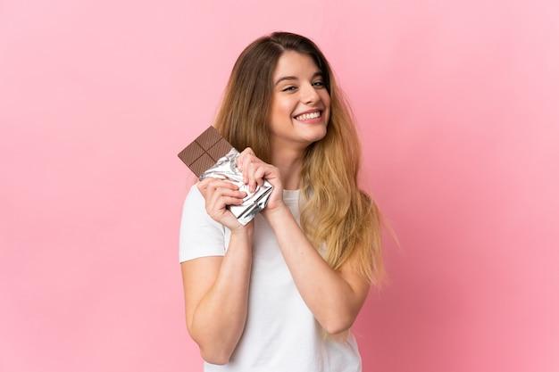 Jonge blonde vrouw over geïsoleerde muur die een chocoladetablet nemen en gelukkig