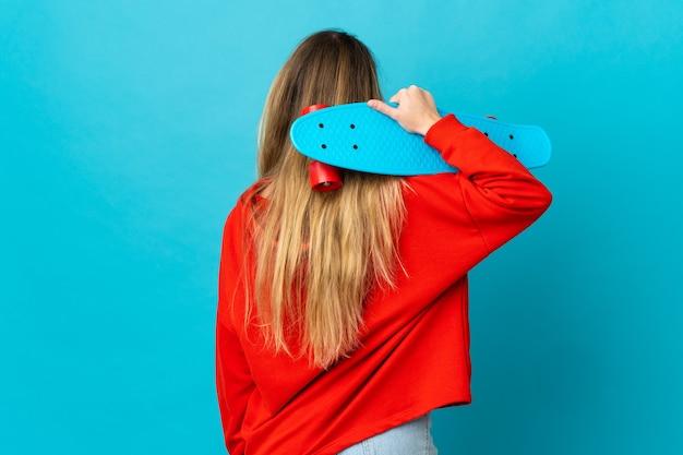 Jonge blonde vrouw over geïsoleerde muur met een schaats in rugpositie