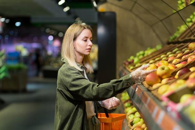 Jonge blonde vrouw plukt kiest fruit groenten op de toonbank in de supermarkt. vrouwelijke huisvrouw winkelen in de markt staan in de buurt van groente warenhuis met een mand in handen. onderzoekt appel