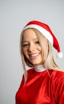 Jonge blonde vrouw poseren in een miss santa claus-kostuum op de grijze muurachtergrond