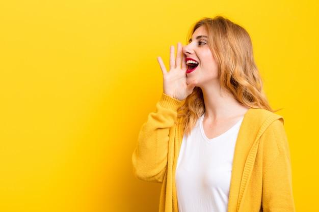 Jonge blonde vrouw profiel weergave, op zoek blij en opgewonden, schreeuwen en bellen om ruimte aan de kant op gele muur te kopiëren