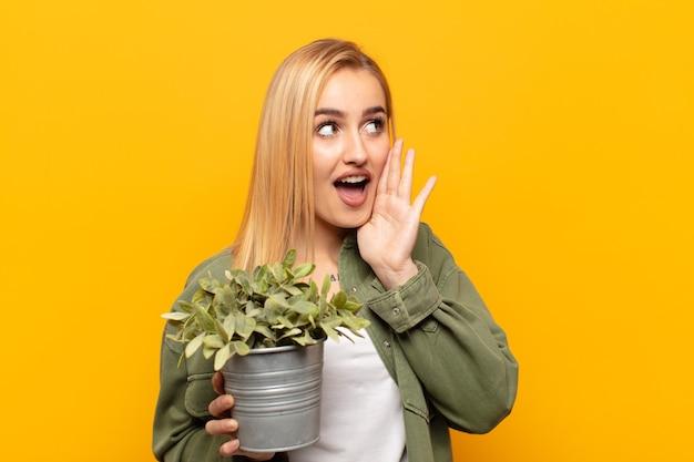 Jonge blonde vrouw profielweergave, blij en opgewonden kijkend, schreeuwend en bellend om ruimte aan de zijkant te kopiëren
