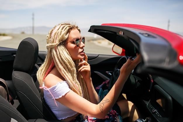 Jonge blonde vrouw rode auto rijden, ongebruikelijke stijlvolle dreadlocks kapsel, heldere vrouwelijke kleding, check haar make-up in spiegel. reisvibes.