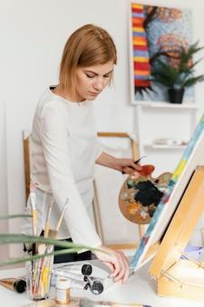 Jonge blonde vrouw schilderen met acrylverf