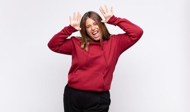Jonge blonde vrouw schreeuwen in paniek of woede, geschokt, doodsbang of woedend, met de handen naast het hoofd