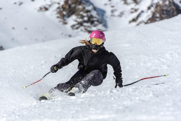 Jonge blonde vrouw skiën op een zonnige dag.