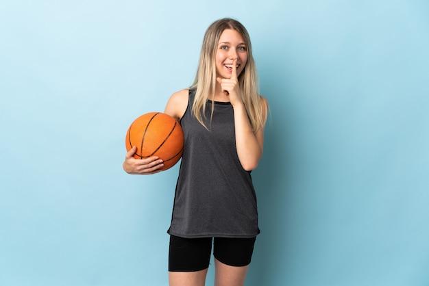 Jonge blonde vrouw speelbasketbal geïsoleerd op blauwe muur doet stilte gebaar