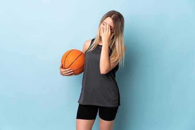 Jonge blonde vrouw speelbasketbal geïsoleerd op blauwe muur lachen