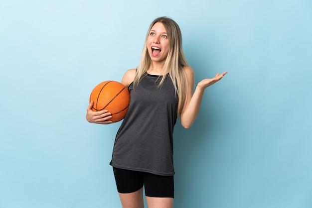 Jonge blonde vrouw speelbasketbal geïsoleerd op blauwe muur met verrassingsgelaatsuitdrukking