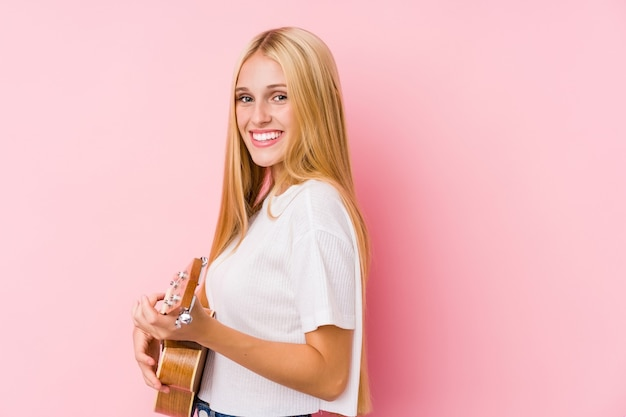 Jonge blonde vrouw speelt ukelele geïsoleerd in een muur