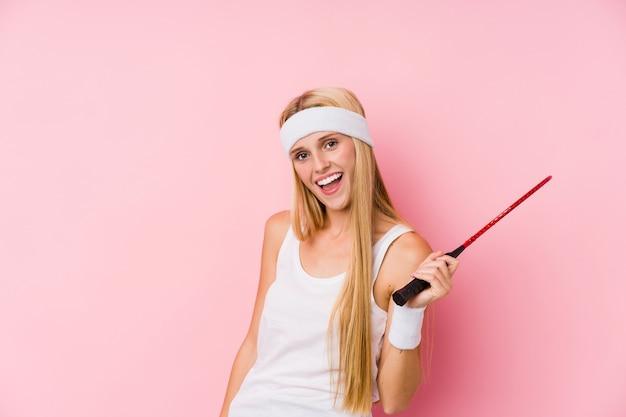 Jonge blonde vrouw spelen badminton geïsoleerd