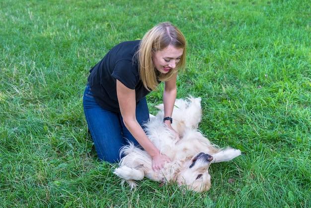 Jonge blonde vrouw spelen met golden retriever hond in het park