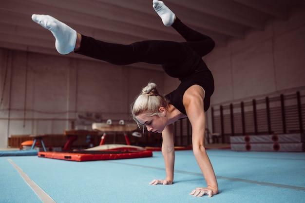 Jonge blonde vrouw training voor kampioenschap turnen