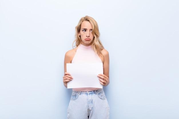 Jonge blonde vrouw verdrietig, boos of boos en op zoek naar de kant met een negatieve houding, fronsen in onenigheid met een vel papier