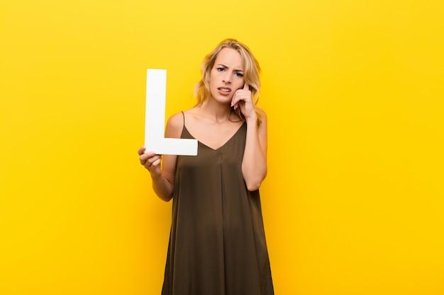 Jonge blonde vrouw verward, twijfelachtig, denken, met de letter l van het alfabet om een woord of een zin te vormen.
