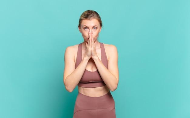 Jonge blonde vrouw voelt zich bezorgd, hoopvol en religieus, bidt trouw met ingedrukte handpalmen en smeekt om vergiffenis. sport concept
