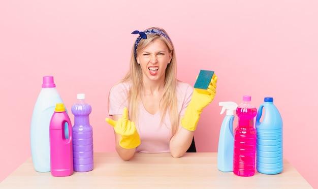 Jonge blonde vrouw voelt zich boos, geïrriteerd, opstandig en agressief. huishoudster concept