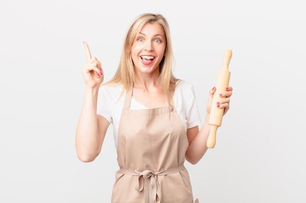 Jonge blonde vrouw voelt zich een gelukkig en opgewonden genie nadat ze een idee heeft gerealiseerd. bakker concept