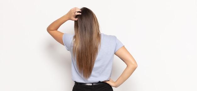 Jonge blonde vrouw voelt zich geen idee en verward, denkt een oplossing, met de hand op de heup en de andere op het hoofd, achteraanzicht