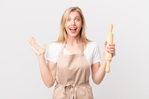 Jonge blonde vrouw voelt zich gelukkig en verbaasd over iets ongelooflijks. bakker concept