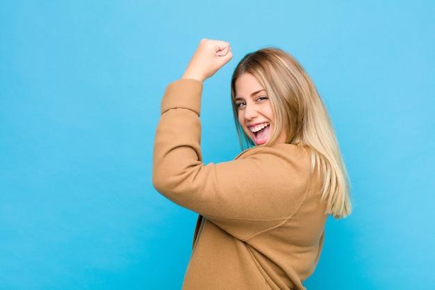 Jonge blonde vrouw voelt zich gelukkig, tevreden en krachtig, buigt fit en gespierde biceps, sterk op zoek naar de sportschool