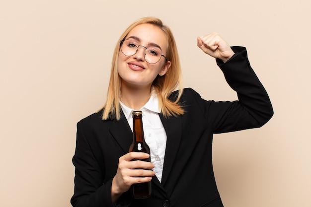Jonge blonde vrouw voelt zich gelukkig, tevreden en krachtig, buigt fit en gespierde biceps, ziet er sterk uit na de sportschool