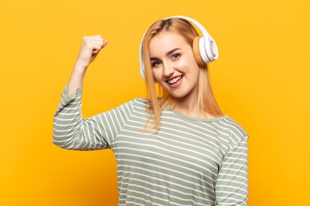 Jonge blonde vrouw voelt zich gelukkig, tevreden en krachtig, buigt fit en gespierde biceps, ziet er sterk uit voor de sportschool