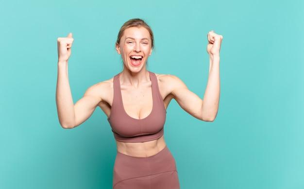 Jonge blonde vrouw voelt zich gelukkig, verrast en trots, schreeuwt en viert succes met een grote glimlach. sport concept