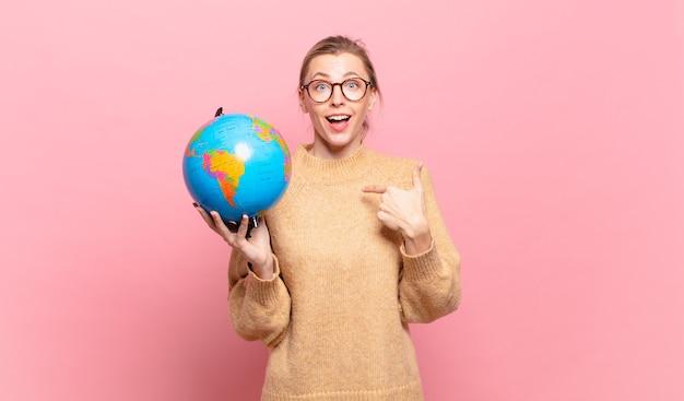 Jonge blonde vrouw voelt zich gelukkig, verrast en trots, wijzend naar zichzelf met een opgewonden, verbaasde blik. wereld concept