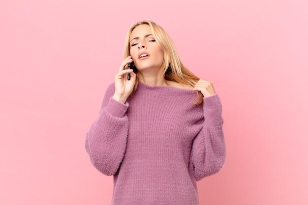 Jonge blonde vrouw voelt zich gestrest, angstig, moe en gefrustreerd en praat met een smartphone