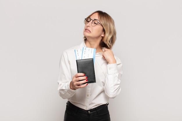 Jonge blonde vrouw voelt zich gestrest, angstig, moe en gefrustreerd, trekt de hals van het shirt aan en kijkt gefrustreerd door het probleem