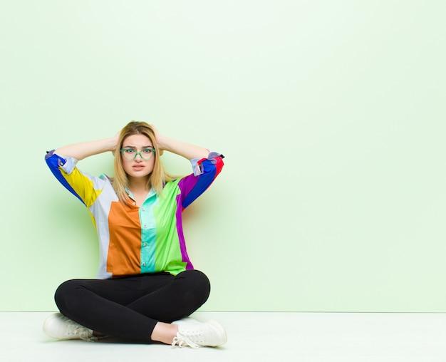 Jonge blonde vrouw voelt zich gestrest, bezorgd, angstig of bang, met de handen op het hoofd, in paniek bij een fout zittend op de vloer