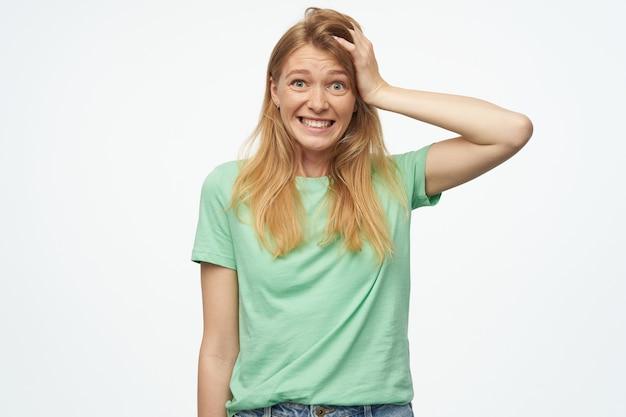 Jonge blonde vrouw, voelt zich gestrest en depressief, houdt haar hand op het hoofd met een geschokte gezichtsuitdrukking