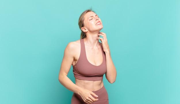 Jonge blonde vrouw voelt zich gestrest, gefrustreerd en moe, wrijft over pijnlijke nek, met een bezorgde, verontruste blik. sport concept