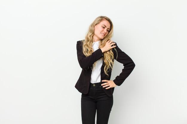 Jonge blonde vrouw voelt zich moe, gestrest, angstig, gefrustreerd en depressief, lijdend aan rug- of nekpijn tegen witte muur