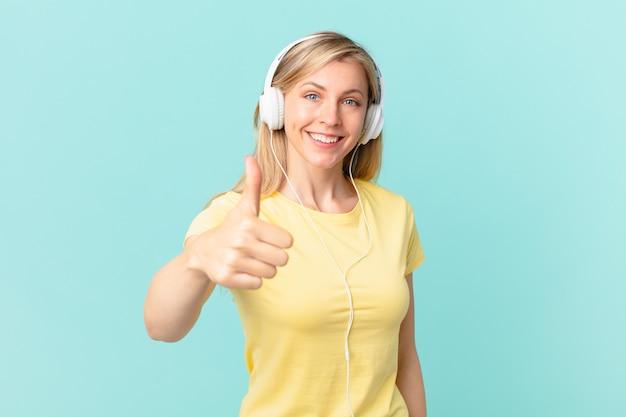Jonge blonde vrouw voelt zich trots, lacht positief met duimen omhoog en luistert naar muziek.