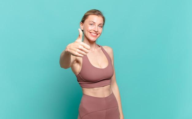 Jonge blonde vrouw voelt zich trots, zorgeloos, zelfverzekerd en gelukkig, positief glimlachend met duimen omhoog. sport concept