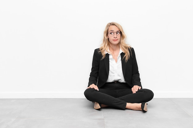 Jonge blonde vrouw vraagt zich af, denkt gelukkige gedachten en ideeën, dagdromen, op zoek naar ruimte aan de zijkant op de vloer zitten