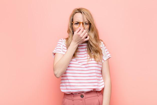 Jonge blonde vrouw walgt gevoel, houdt neus om te voorkomen dat een vieze en onaangename stank op een egale kleur muur ruiken