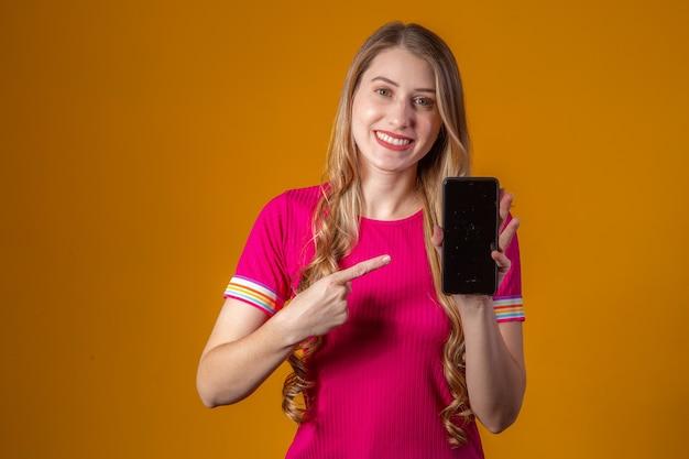 Jonge blonde vrouw wijzend naar mobiele telefoon.