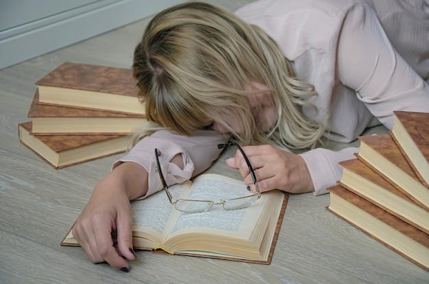 Jonge blonde vrouw wordt omringd door boeken die tijdens het studeren op de grond in slaap waren gevallen