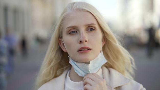 Jonge blonde vrouw zet haar medische masker neer, drinkt koffie en zet het masker weer op op straat. close-up, 4k uhd.