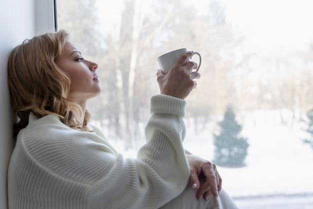 Jonge blonde vrouw zit bij het raam met winterlandschap. een gezellig tijdverdrijf.