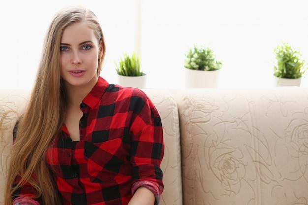 Jonge blonde vrouw zit vroeg in de ochtend op de bank in de kamer. dromen interieur plezier concept