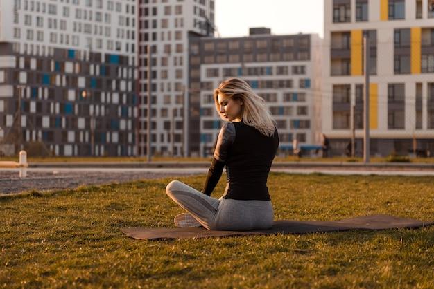 Jonge blonde vrouw zitplaatsen op speelplaats op een yogamat. flatgebouwen en zonsondergang op de achtergrond. gezond energetisch actief levensstijlconcept.