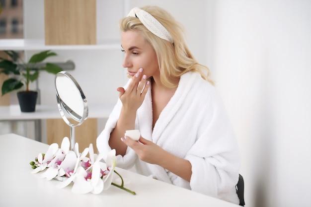 Jonge blonde vrouw zittend aan de tafel lotion toe te passen